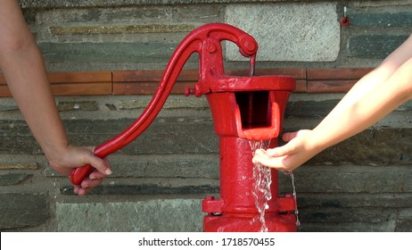 female hand move red water hand pump extracting water to child's hands
