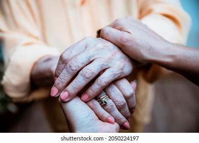Female Hand in old lady Hand, closeup. Holding Elderly hands for support. Have Empathy and Compassion to Senior people