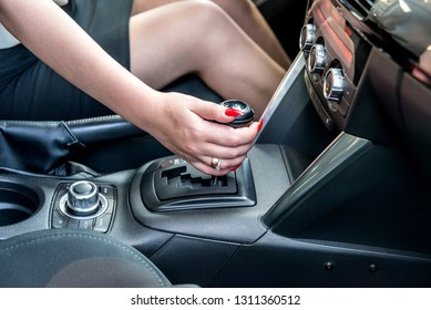 Female hand on automatic transmission lever, close up