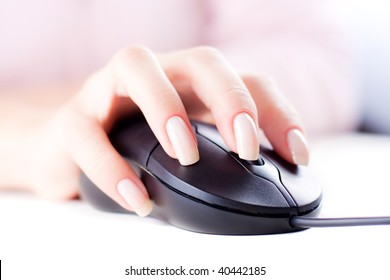 Female hand on computer mouse. Selective focus. White background