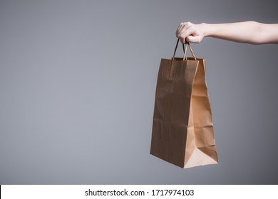 Female hand on a gray background holds out or picks up a paper bag with handles. Advertising shooting for a company with delivery - Shutterstock ID 1717974103