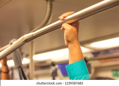Female hand on to pole in train
