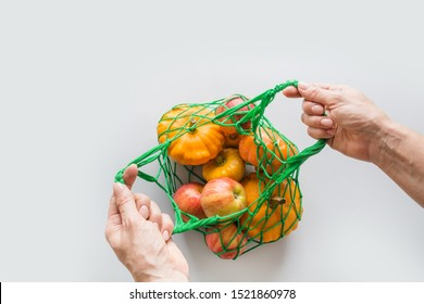 Female hand open shopping mesh bag with pumpkins and apples on grey. Zero waste concept. Space for text. Fall harvest.