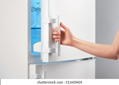 Female hand opening white refrigerator door on gray background