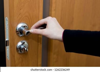 Female hand opens the interior door close-up