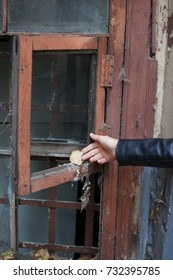 A female hand opens the window in an old abandoned house