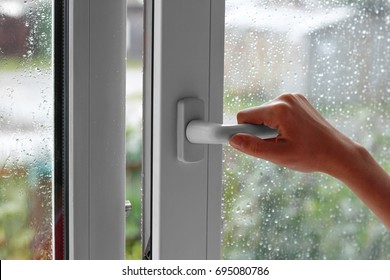 A female hand opens a window with water drops. Closes the window. In the rainy weather. Closeup.