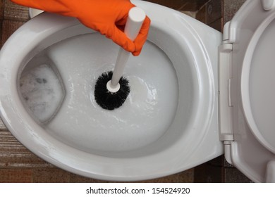Female hand in orange rubber glove cleaning toilet bowl using brush. Clean up your house.