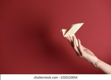 Female hand with origami bird on color background