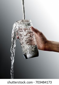 Female hand with overflowing glass of water on grey gradation