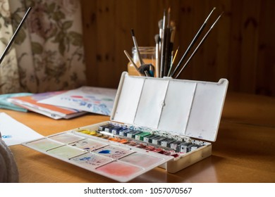 Female hand painting with a brush and paints a picture