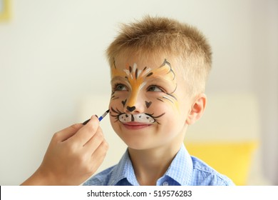 Female hand painting face of funny boy