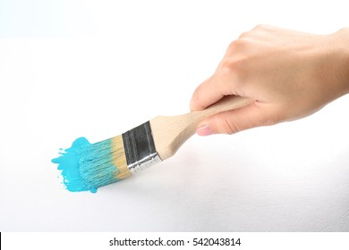 Female hand painting white wall with brush