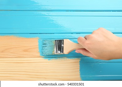 Female hand painting wood with brush