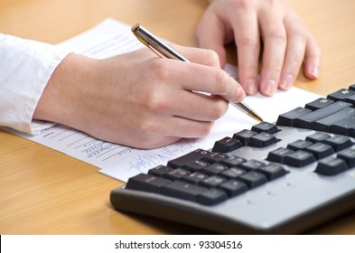 Female hand with pan writing on the paper nearkeyboard on the table