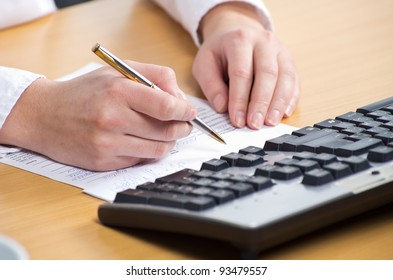 Female hand with pan writing on the paper near keyboard on the table