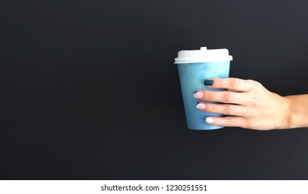 Female hand with paper cup of coffee on dark wall background. Place for your text or logo.