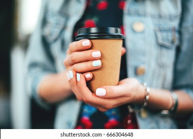Female hand with paper cup of coffee take away.