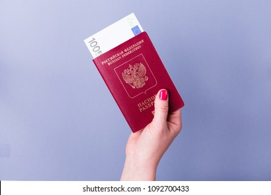 Female hand with a passport with euro banknotes on a blue background
