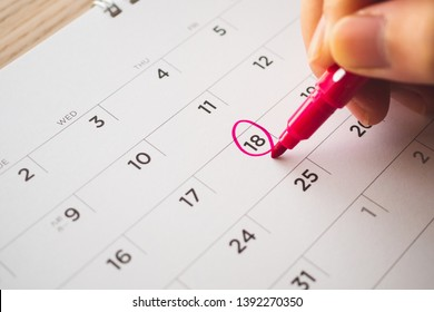 Female Hand with pen mark on calendar date