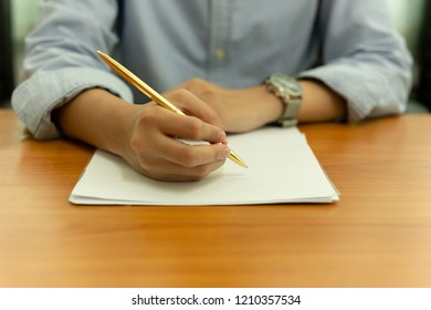 Female hand with pen on document form on wooden table.
