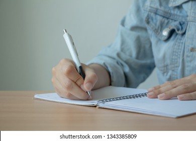 Female hand with pen writing on notebook.
