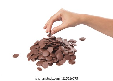 Female hand picking up chocolate button over white background