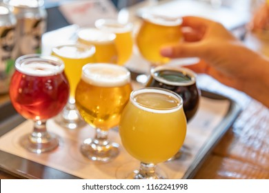 Female Hand Picking Up Glass of Micro Brew Beer From Variety on Tray
