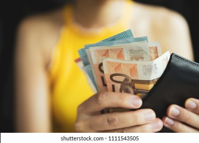 A female hand piking up or counting money in the wallet. Budget for travelling or purchacing.