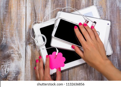 Female hand with pink manicure reaching for cell phone. Digital detox or gadget addiction concept