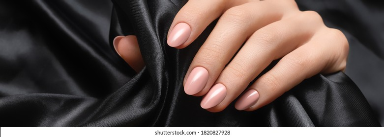 Female hand with pink nail design. Woman hand on black fabric background. Advertising banner ad.