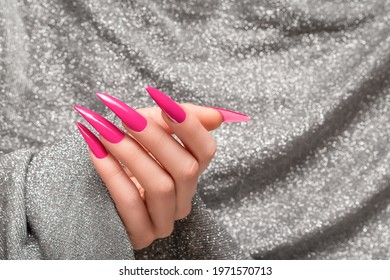 Female hand with pink stiletto nail design. Long nail polish manicure. Woman hand on glitter silver fabric background.