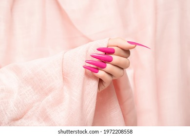 Female hand with pink stiletto nail design. Long nail polish manicure. Woman hand on glitter pink fabric background.