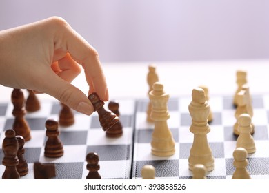 Female hand playing chess on light blurred background