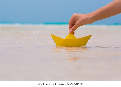 Female hand playing with paper boat in water on the white sand beach on blue sea background