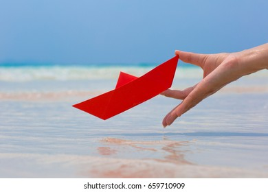 Female hand playing with red paper boat in water on the white sand beach on blue sea background