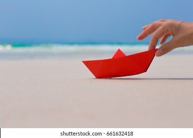 Female hand playing with red paper boat on the beach on blue sea background