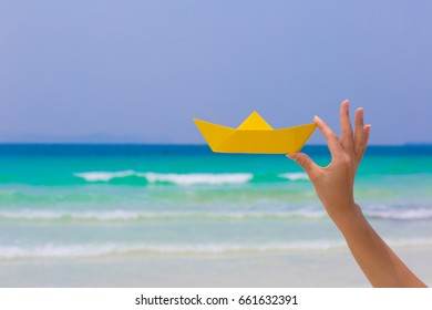 Female hand playing with yellow paper boat on the beach on blue sea background
