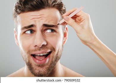 Female hand plucking scared men's eyebrows with tweezers isolated over gray background