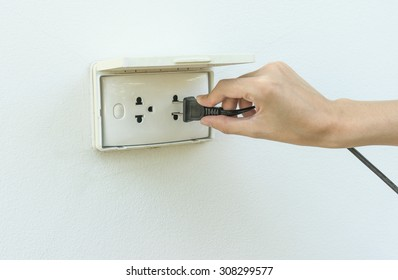 Female hand plugging in appliance to electrical outlet in wall