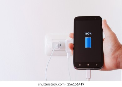 female hand plugging in the wall electtric plug of her smartphone in a socket.Power is not enough for human