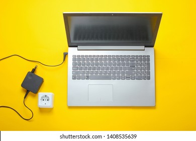 Female hand plugs a laptop charger into an electrical outlet on yellow background