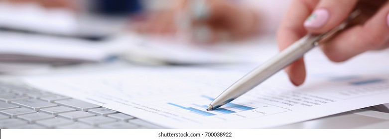 Female hand point silver pen to graph on seminar. Bank credit, loan money, invest, tax situation review, income calculation form, white collar train, investment audit, board members session concept