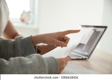 Female hand pointing on document paying attention to important term considering contract, couple holding papers analyzing deal conditions protecting from fraud, reading instructions report, close up