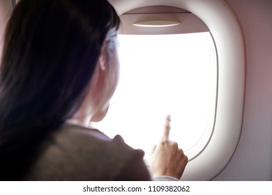 Female Hand Pointing Out of Plane Window