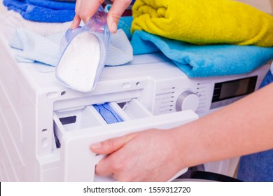 Female hand pour the washing powder detergent into machine.