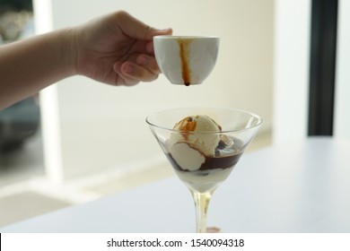 Female hand pouring coffee in the glass of affogato coffee: espresso shot with vanilla ice cream on white table, side view.