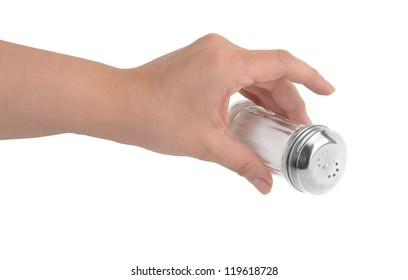 Female hand pouring salt from salt shaker
