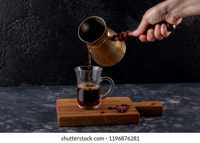 Female hand pouring traditional Turkish coffee. Cup and pot of coffee and coffee beans on a wooden board.