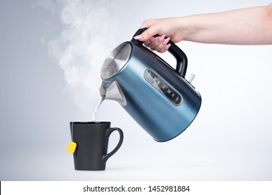 Female hand pours hot water from an electric kettle into a black mug, on light background.